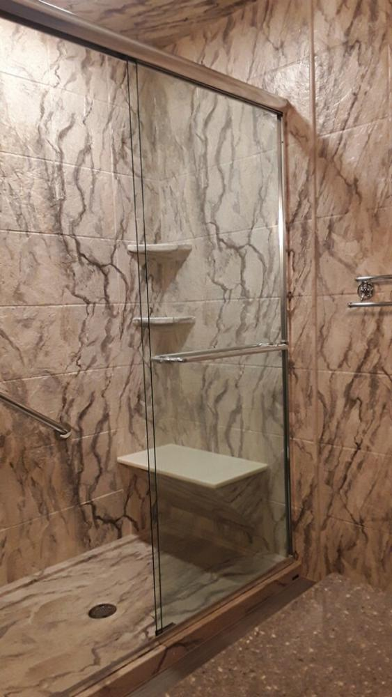 The shower light showcases the Durabath Sandstone walls and base.  The wall continues outside the wet area.