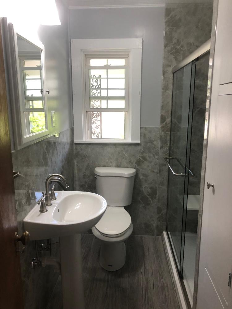 Light Grey Emperador Acrylic not only inside the shower but continues as wainscoting throughout the room.  The tub was turned into a low threshold full bench seated shower.  Bright white features and accessories compliment the color of walls and grey vinyl plank tile.