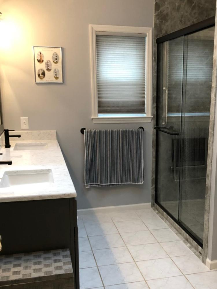 The dropped soffit has been removed and the new Grey emperador walls extent to the ceiling.  this give the bathroom a larger anfell and makes it lighter.  The new vanity has a Quartz top and rectangular sinks.