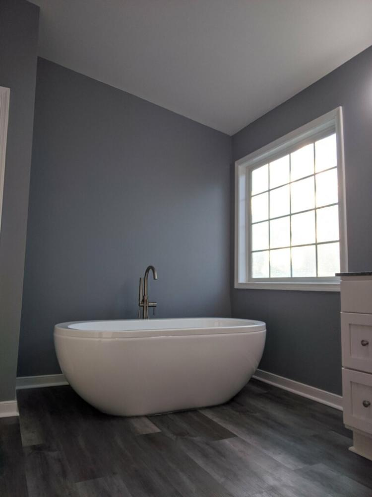 We took out a corner garden tub and installed a Free Standing Tub.  We also replaced the floor with a luxury Vinyl Plank.  Our team also painted the walls for a completed bathroom.