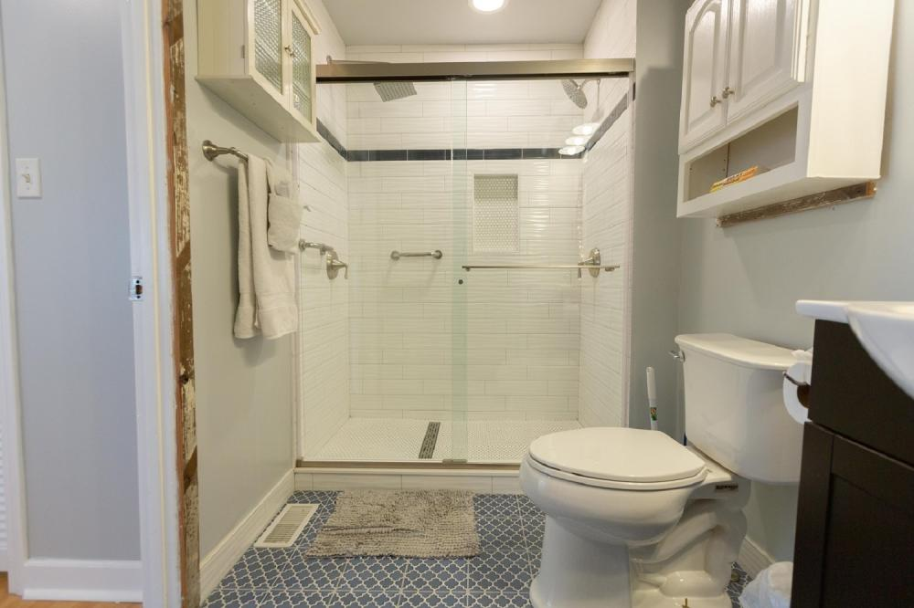 Walk in Double shower with lateral drain and dual rain showers with safety grab bars
